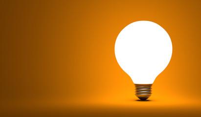 Shining globe light bulb on orange