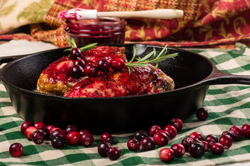 Two cranberry glazed chicken breasts in pan
