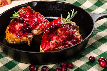 Two cranberry glazed chicken breasts in skillet