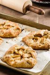 Tray of apple tarts with rolling pin