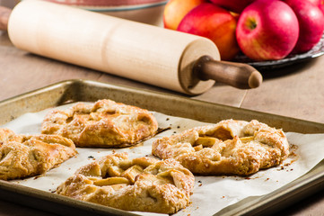 Warm apple tarts with rolling pin
