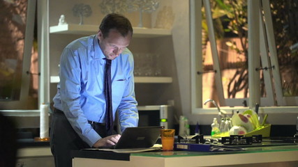 Young businessman working on laptop in kitchen at home at night