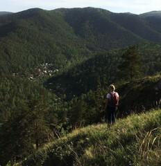 Девушка с рюкзаком на пргулке в горах