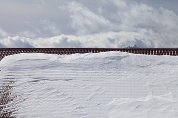 Snowy roof and cloudy sky