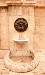 Old broken drinking fountain in the Spanish city. Tinted