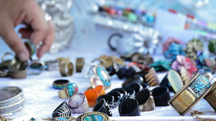 Putting rings and jewelry on a street stall selling crafts