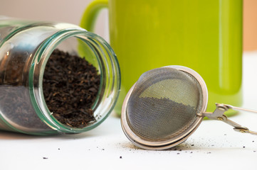 Filled tea infuser jar with tea inside and a green cup