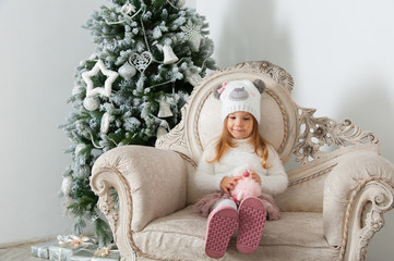 Child girl in bear hat with sheep toy