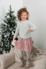 Child girl jump with sheep toy at Christmas