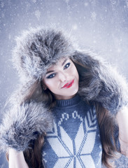 Winter beauty woman in a fur hat and mittens over snowy backgrou