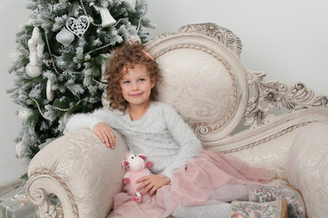 Pretty child girl with sheep toy near Christmas tree
