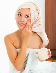 Girl applying cream on face