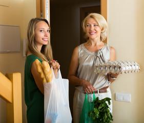 Women with bags of food near door