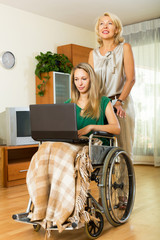 Girl in wheelchair with female assistant  at home