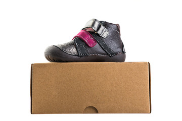 Grey baby's shoe on the box isolated  on white background