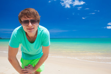 young man in sunglasses smiling at beach