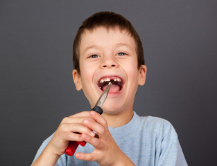 Boy simulates tooth removal with pliers