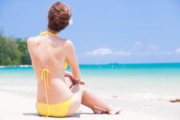 long haired woman in straw hat in bikini on tropical beach