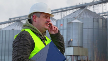 Worker with folder and cell phone near the factory
