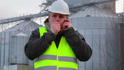 Worker with cell phone near the factory in winter