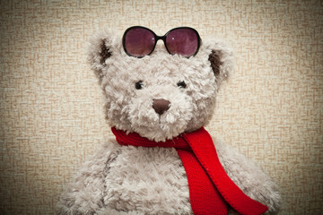 Teddy bear in a red scarf and sunglasses