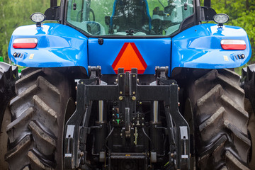 Huge rear wheels of the blue new tractor