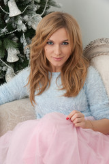 Blonde young woman sit near Christmas tree