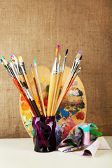 Paint brushes with paints and palette on beige background