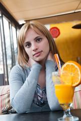 Cuttest blond on earth in coffee shop drinking orange juice
