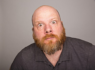 wild eyed bald man with full red beard