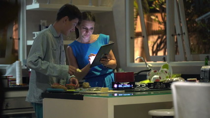 Mother with son preparing food, talking and using tablet