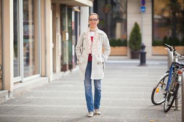 Beautiful young woman walking down the city street