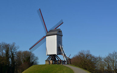 Old windmills are symbols of belgian bruges.