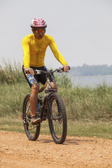 young man wearing rider suit riding mountain bike MBT on dusty r