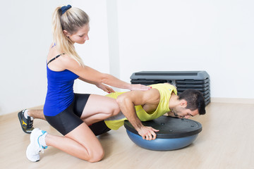 Weiblicher Trainer hilft bei Fitness-Übung