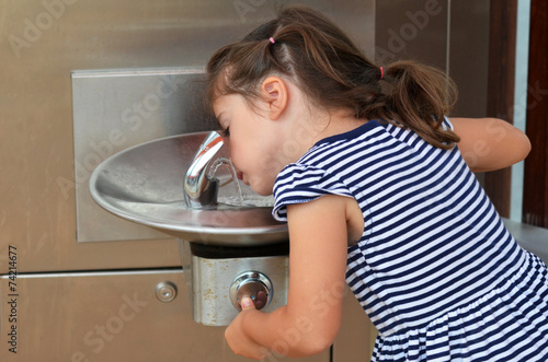 Child Drinking From Outdoor Water Fountain - 74214677
