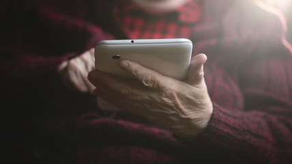 Hands of the old woman and electronic tablet