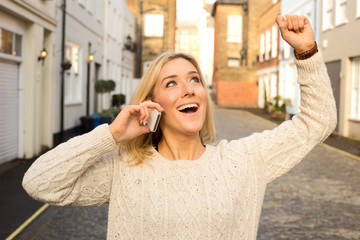 young woman celebrating on the phone