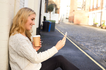 young woman checking her messages with a coffee