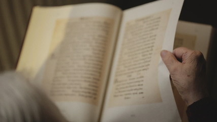 SLOW MOTION: Old human reading a book. Close up
