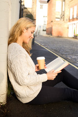 young woman reading a book and drinking a coffee