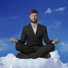 Young man sitting on cloud meditating