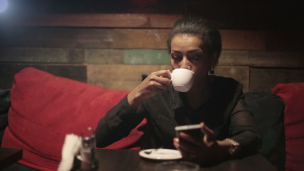 Black woman drinking hot coffee and use smartphones