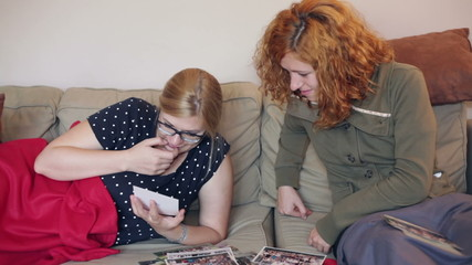 Girlfriends looking at photos and relaxing on sofa at home.