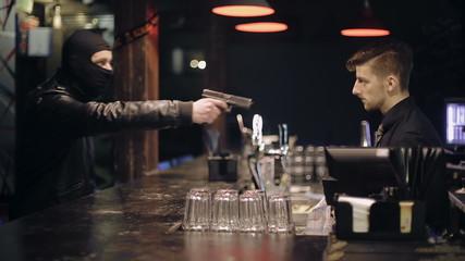 Unsuccessful robbery bar. The barman also has a gun