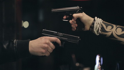 Two male hands with guns take aim at each other. Close up