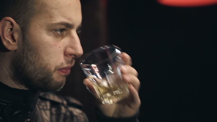 The man at the bar drinking whiskey with ice
