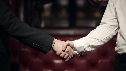 Business partners men doing a handshake. Slow motion