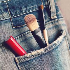 Closeup makeup tools in back jeans pocket