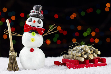 Snowman and sled on bokeh lights background